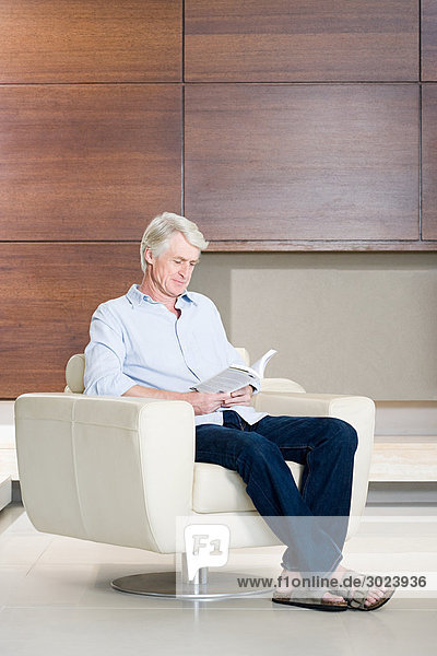 Middle aged man sitting in chair reading book