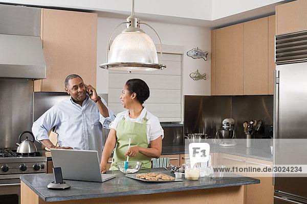 Paar in der Küche mit Laptop und Handy