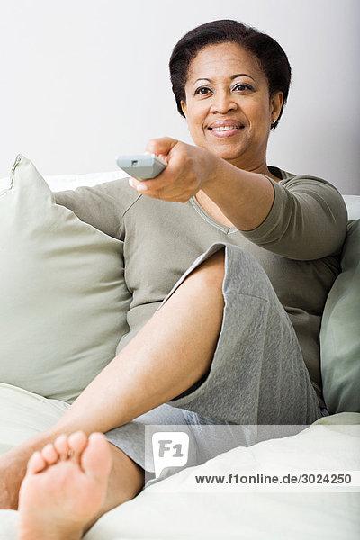 Frau auf Sofa mit Fernbedienung