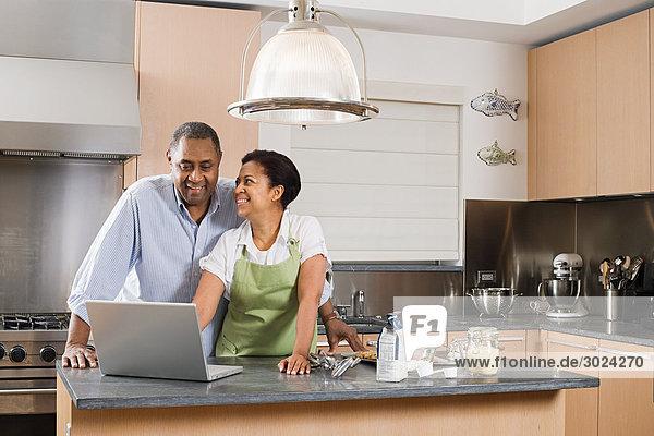 Paar in der Küche mit Laptop