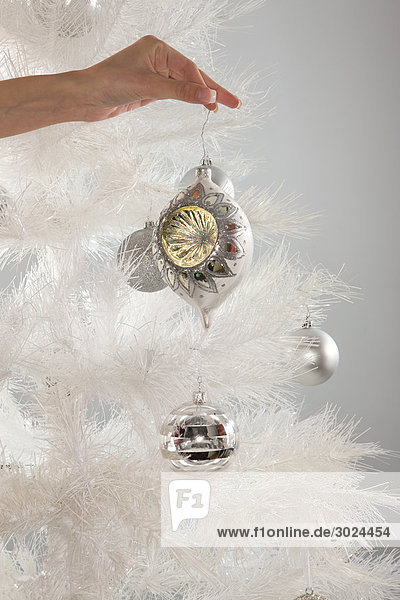 Woman placing a decoration on christmas tree