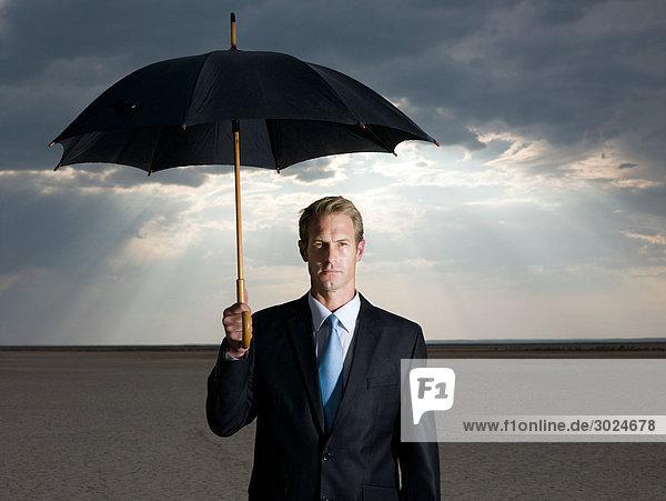 Geschäftsmann in der Wüste mit Regenschirm