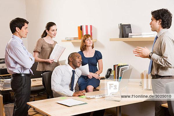 Fünf Büroangestellte in einer Besprechung