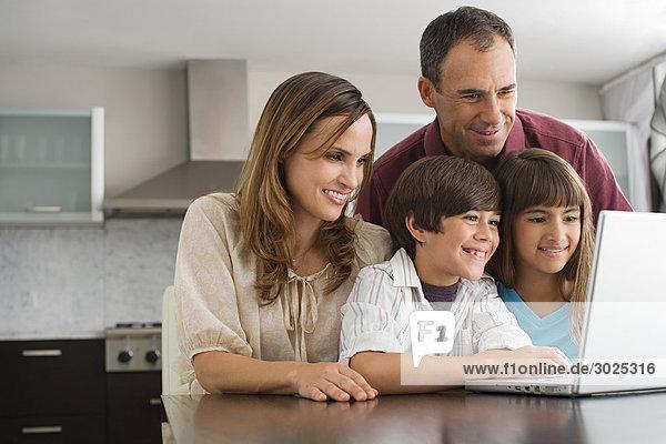 Familie  die einen Laptop benutzt