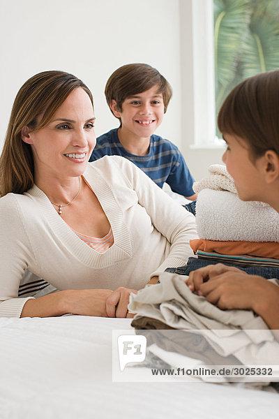 Mutter und Kinder auf dem Bett sitzend