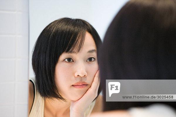 Japanerin schaut in den Spiegel