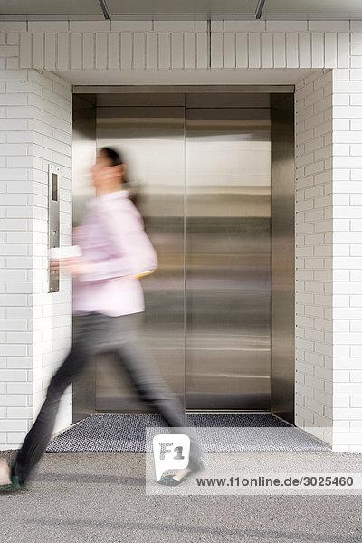 Blurred woman walking past elevator
