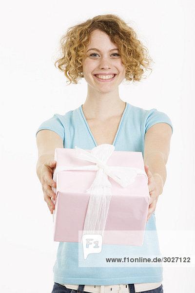 Junge Frau mit Geschenkpaket  lächelnd  Portrait