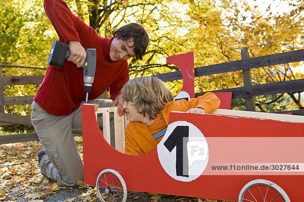 Austria  Salzburger Land  Young man fixing soapbox car  boy (12-13) watching