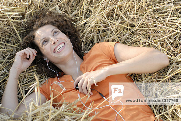 Young woman with MP3 player relaxing in hay  smiling  portrait
