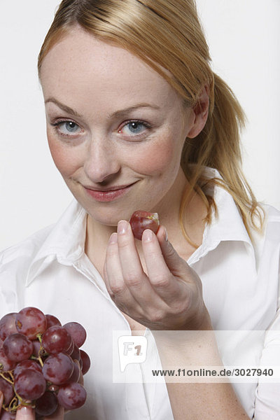 Young woman holding grapes  smiling  portrait