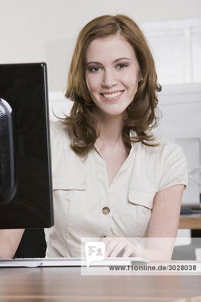 junge Frau  die im Büro arbeitet  lächelnd  Portrait