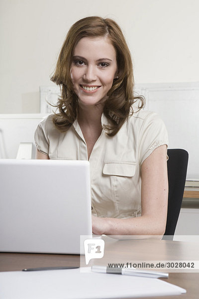 young woman in office  using laptop  smiling  portrait