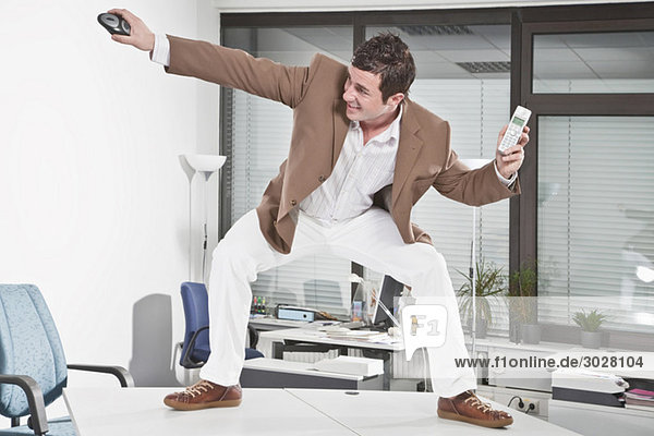 Germany  Business man standing on desk  holding phone and mouse