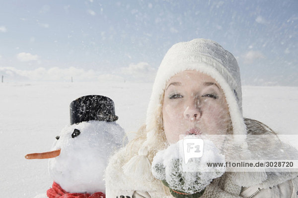 Young woman blowing snow off hand  portrait