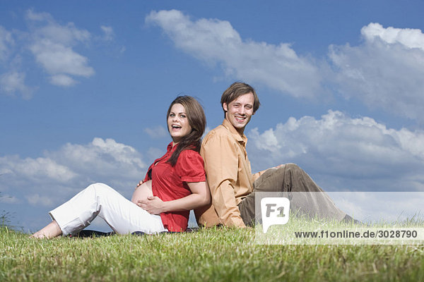 Couple sitting back to back in meadow  smiling  portrait