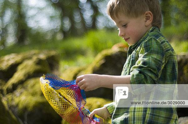 Junge (4-5) hält Dip-Netz  Seitenansicht Junge (4-5) hält Dip-Netz, Seitenansicht