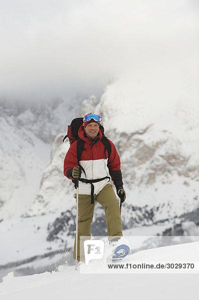 Italien  Südtirol  Mann Schneeschuhlaufen  lächelnd