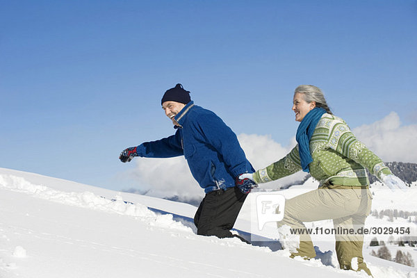Italien  Südtirol  Seiseralm  Seniorenpaar zu Fuß im Schnee  Seitenansicht  Portrait