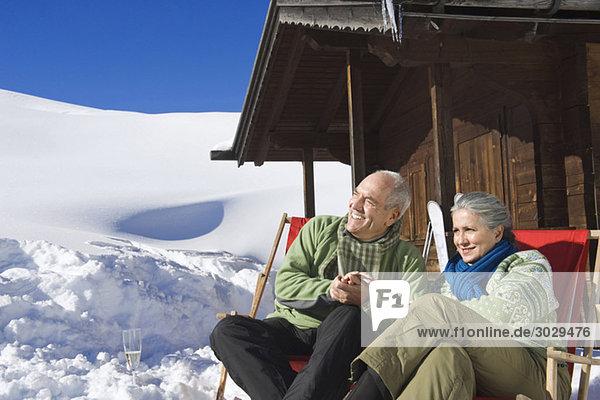 Italien  Südtirol  Seiseralm  Seniorenpaar vor Blockhaus sitzend  lächelnd  Portrait