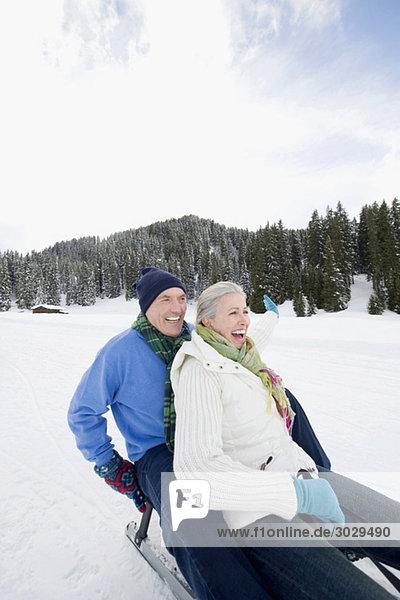 Italien  Südtirol  Seiseralm  Seniorenpaar Rodeln  Lachen  Portrait