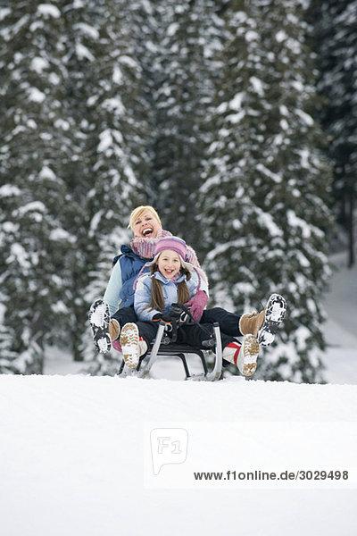 Italien  Südtirol  Seiseralm  Mutter und Tochter (6-7) beim Schlittenfahren  Lachen  Porträt