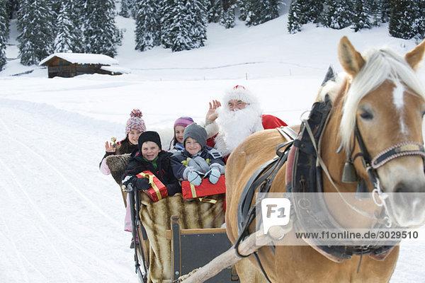 Italien  Südtirol  Seiseralm  Weihnachtsmann und Kinder sitzen im Schlitten