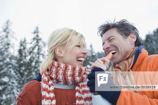 Italien  Südtirol  Seiseralm  Paar lächelnd  Mann mit Karotte  lächelnd  Portrait  Nahaufnahme
