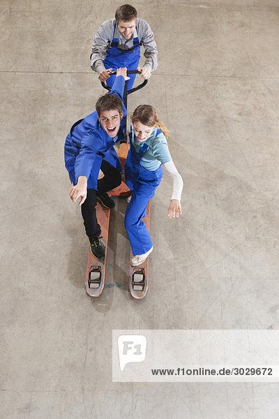 Deutschland  Neukirch  Ausbilder und Auszubildende in der Industriehalle  herumalbern  erhöhte Aussicht