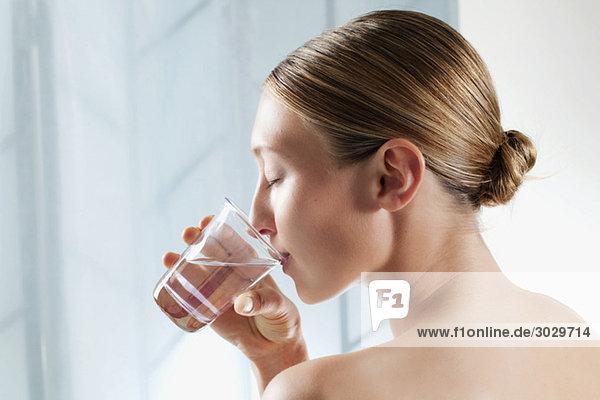 Junge Frau trinkt ein Glas Wasser  Augen zu  Portrait