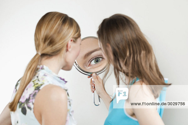 Young women looking into mirror