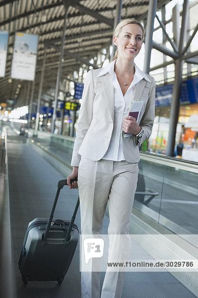 Junge Frau mit Koffer auf dem Fahrsteig