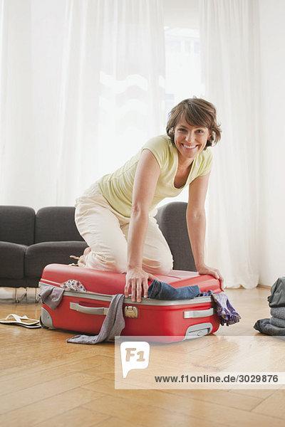 Frau kniend auf dem Koffer  lächelnd  Porträt