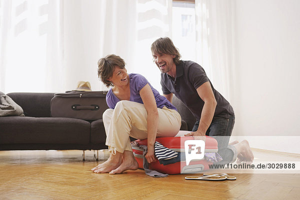 Germany  Leipzig  Couple packing a suitcase  laughing