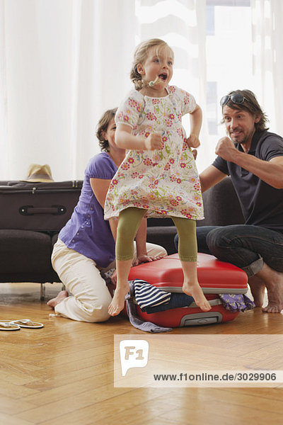Girl (4-5) jumping  father and mother packing suitcase in background