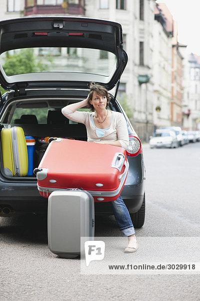 Frau sitzt hinten im Auto und hält den Koffer.