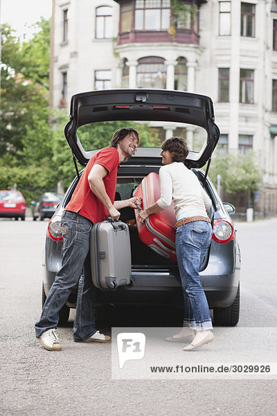 Germany  Leipzig  Couple loading luggage into car