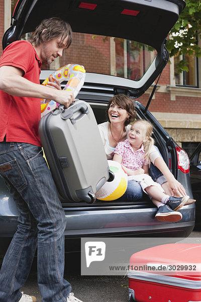 Germany  Leipzig  Family loading luggage into car