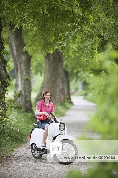 Junger Mann auf Moped  lächelnd  Portrait Junger Mann auf Moped, lächelnd, Portrait