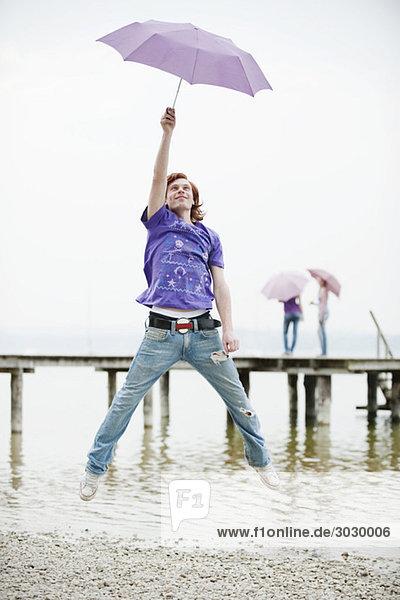 Junger Mann mit Regenschirm und Springen
