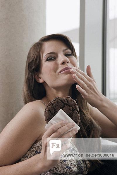 Junge Frau hält ein Stück Kuchen  Porträt
