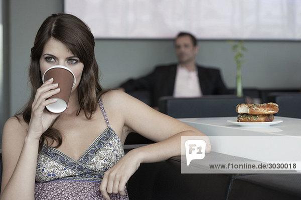 Junge Frau im Café trinkt Kaffee  Mann im Hintergrund