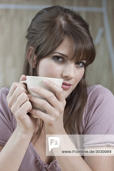 Young woman holding cup of coffee  portrait