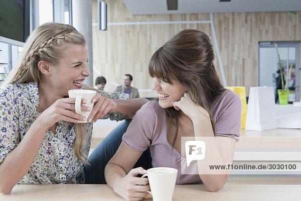 Junge Frauen im Cafe  Spaß haben