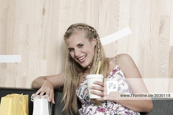 Junge Frau hält Getränk  lächelnd  Portrait