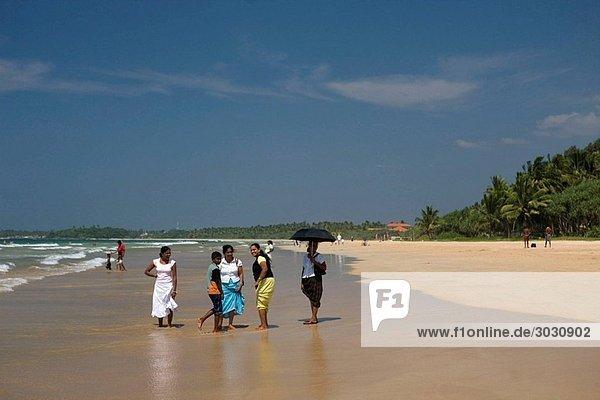 Local women walking along Bentota Beach  Sri Lanka