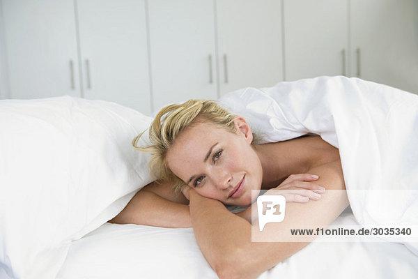 Nahaufnahme einer Frau auf dem Bett liegend und lächelnd
