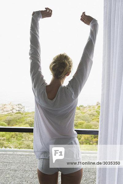 Rückansicht einer Frau  die ihre Arme auf dem Balkon ausstreckt.