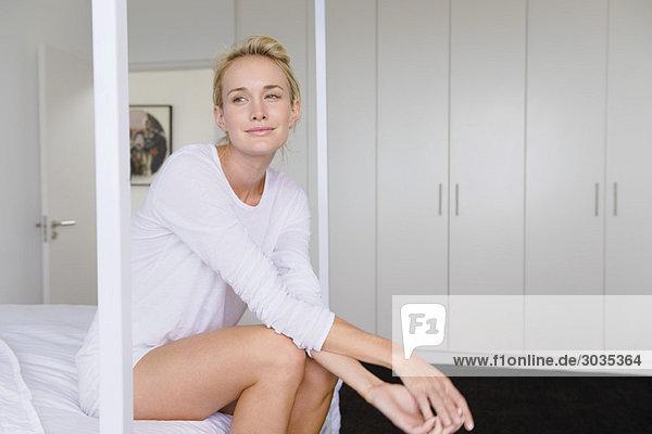 Frau auf dem Bett sitzend und lächelnd
