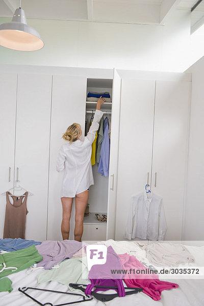 Frau bei der Kleiderauswahl im Kleiderschrank